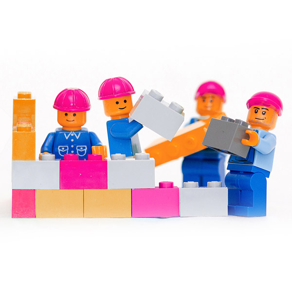 Lego men building a brick wall